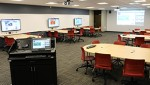 Classroom with group tables and television screens for each group table