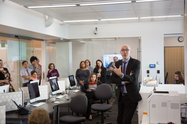 Interior of MMLC Lab, with computer workstations visible. Dean Andrian Randolph is standing addressing standing faculty and staff guests